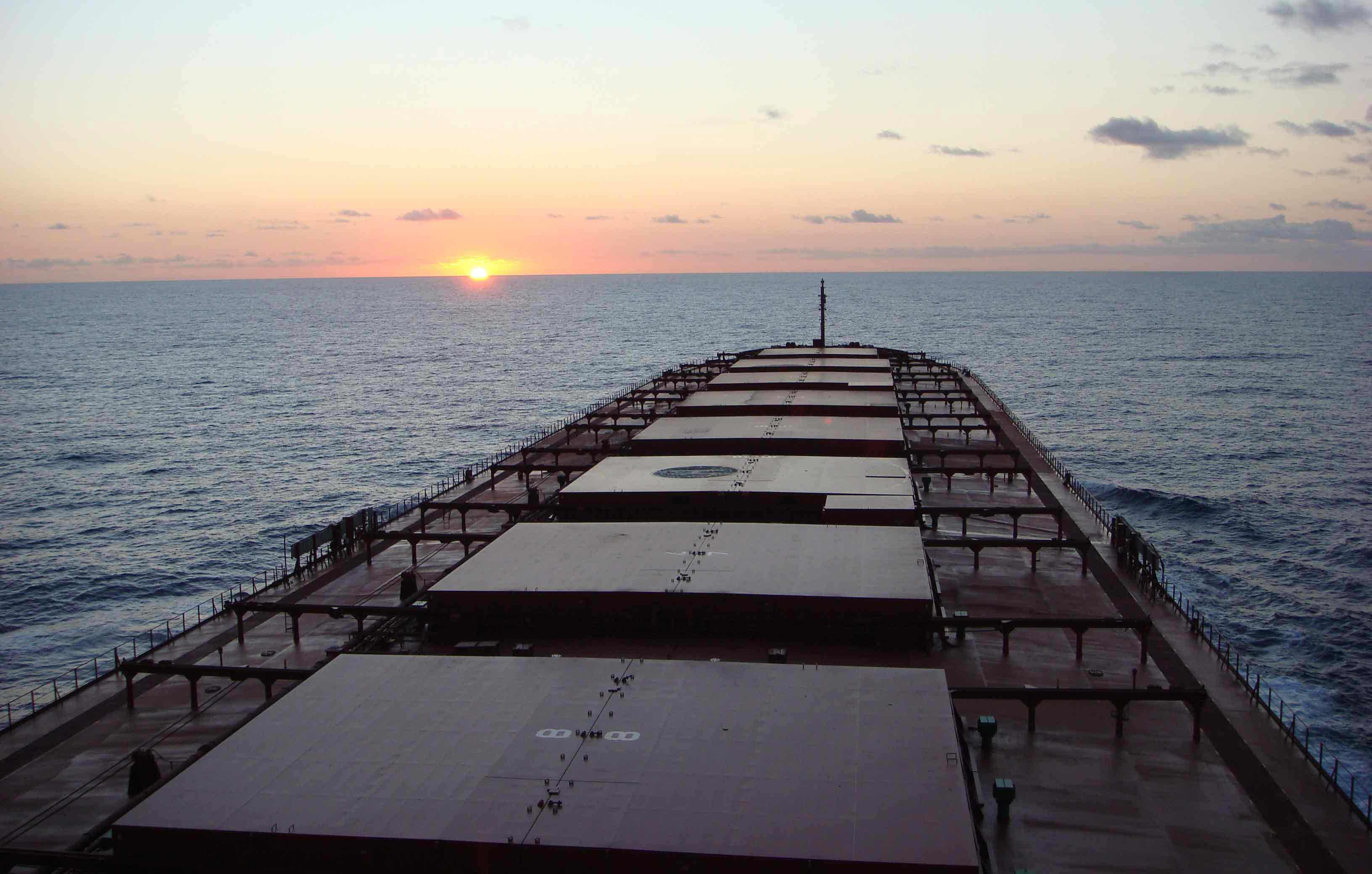 Sun setting behind an Ofer Global ship